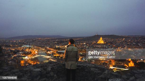 rear view of man standing on mountain against sky at night - トビリシ ストックフォトと画像
