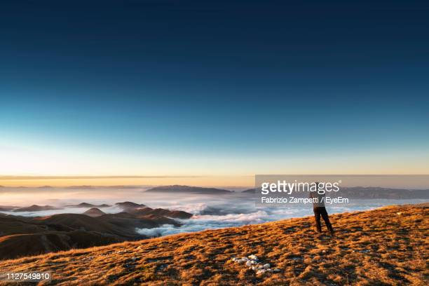 rear view of man standing on mountain against sky during sunset - fabrizio zampetti foto e immagini stock