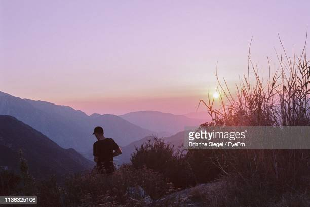 rear view of man standing on mountain against sky during sunset - brianne stock pictures, royalty-free photos & images