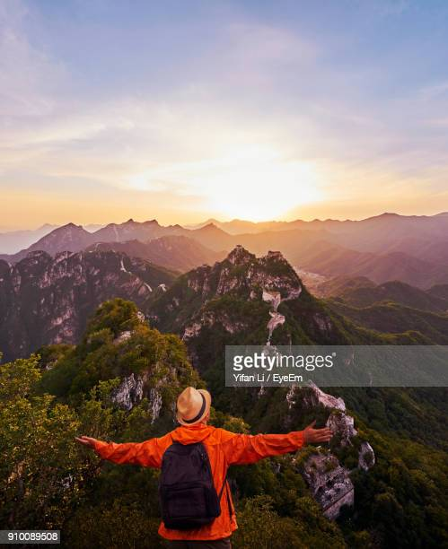 rear view of man standing on mountain against sky during sunset - tranquil scene stock pictures, royalty-free photos & images