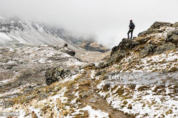 Rear View Of Man Standing On Mountain Against Sky During Winter