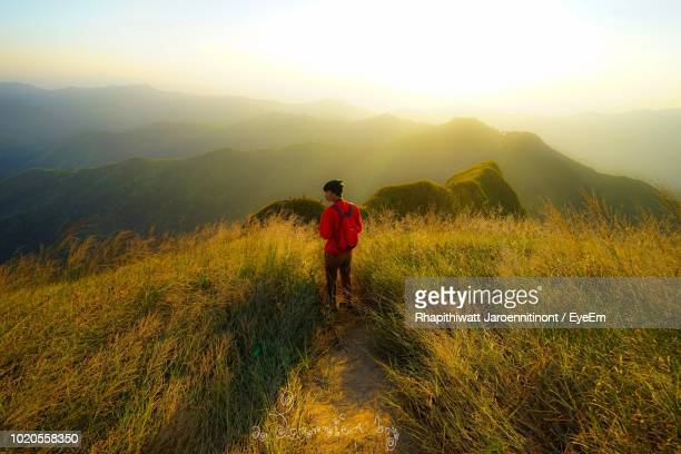 rear view of man standing on mountain against sky - カンチャナブリ県 ストックフォトと画像