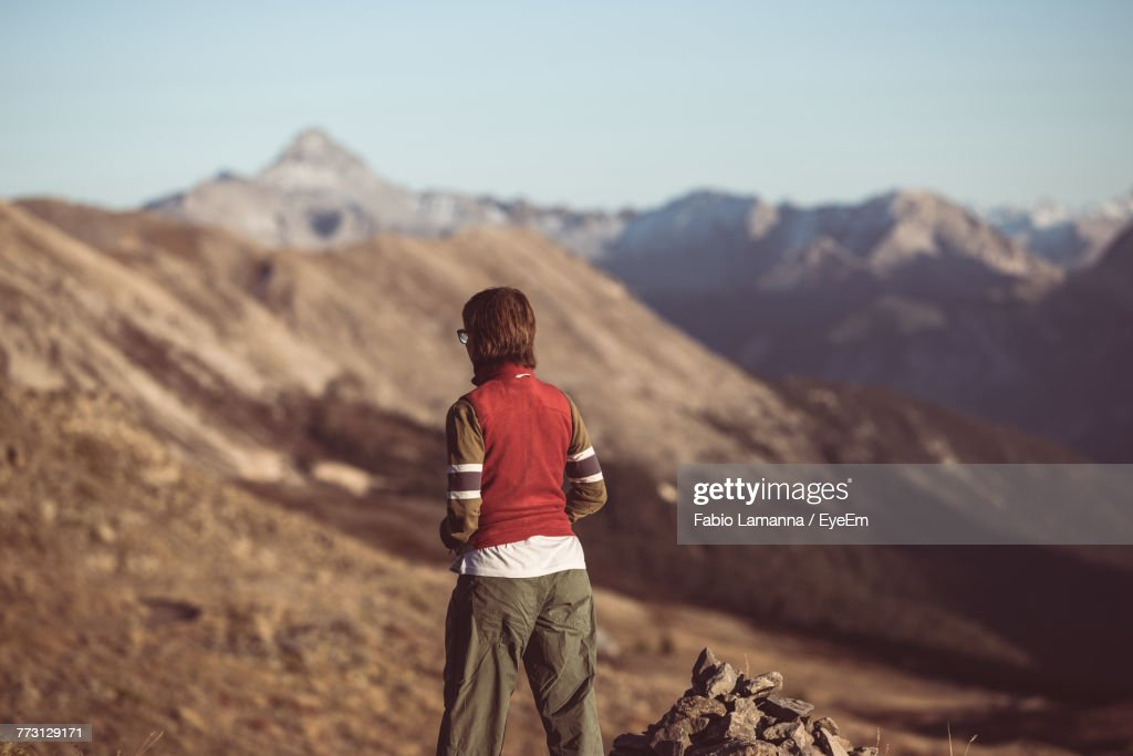 Rear View Of Man Standing On Mountain Against Sky : Photo