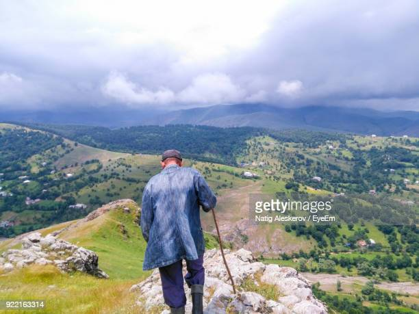 rear view of man standing on mountain against sky - azerbaijan stock pictures, royalty-free photos & images