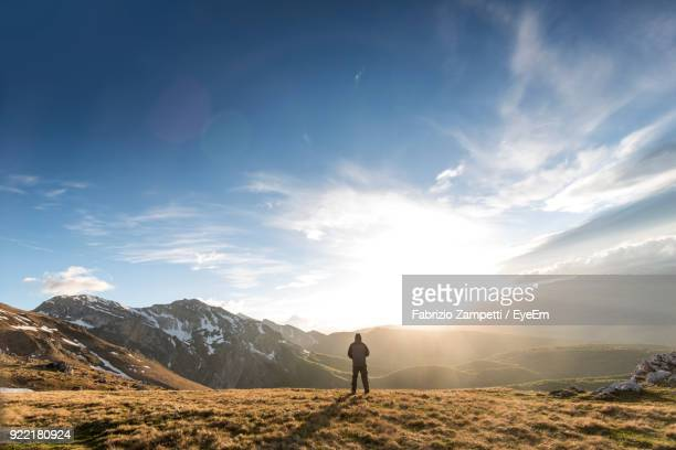 rear view of man standing on mountain against sky - fabrizio zampetti foto e immagini stock