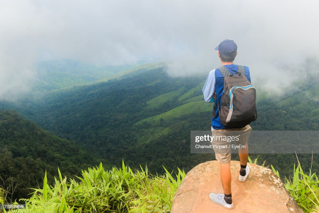 Rear View Of Man Standing On Mountain During Foggy Weather : Photo