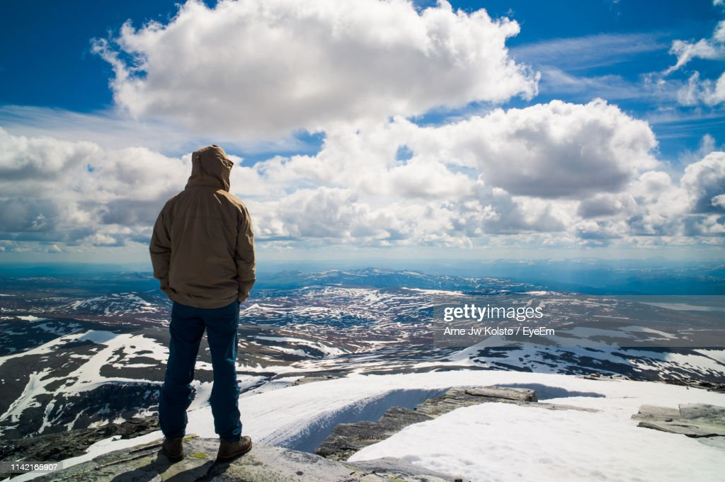 Rear View Of Man Standing On Mountain During Winter : Stock Photo