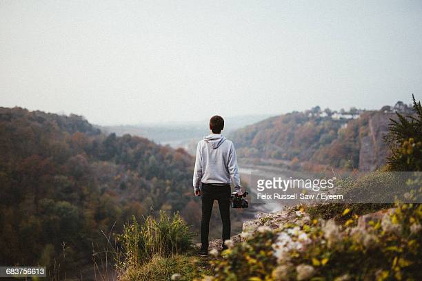 Rear View Of Man Standing On Mountain In Forest