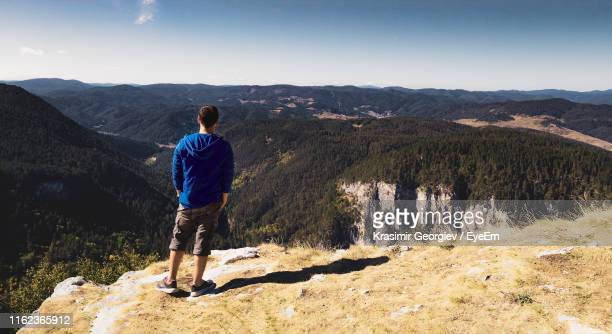 rear view of man standing on mountain - krasimir georgiev stock photos and pictures