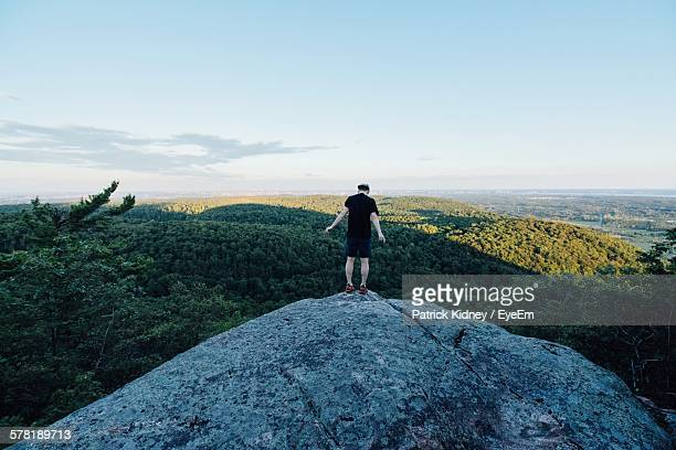 rear view of man standing on mountain - gatineau stock photos and pictures