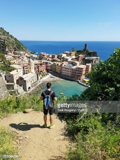 rear view of man standing on mountain while looking at view - cinque terre stock pictures, royalty-free photos & images