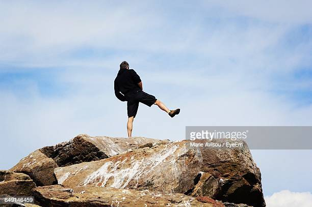 Rear View Of Man Standing On One Leg At Rock Formation