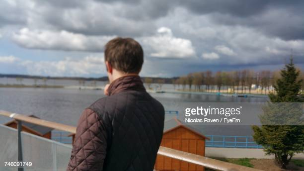 Rear View Of Man Standing On Pier By Lake Against Cloudy Sky