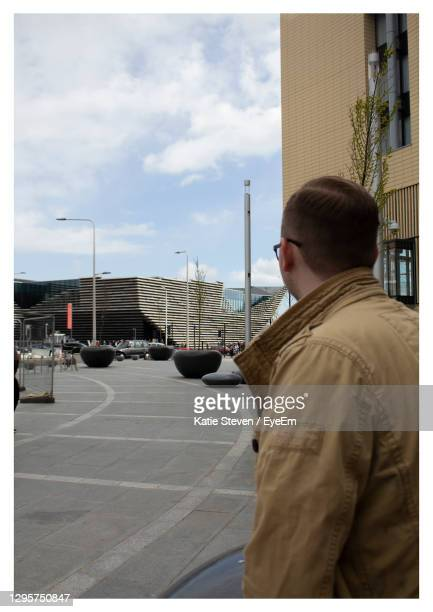 rear view of man standing on road against sky - dundee scotland stock pictures, royalty-free photos & images