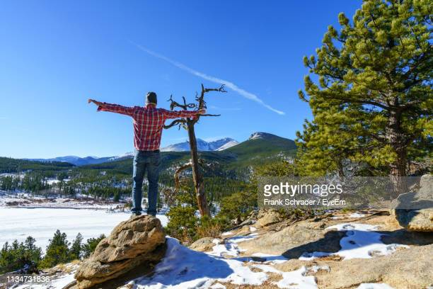 Rear View Of Man Standing On Rock Against Mountains During Winter