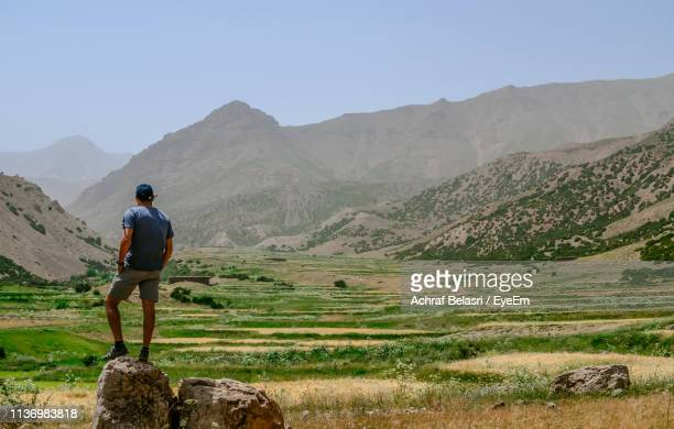 Rear View Of Man Standing On Rock Against Mountains