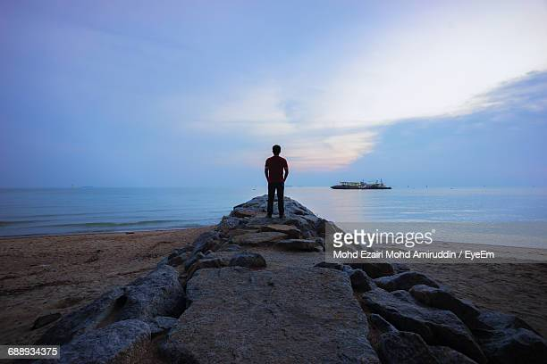 Rear View Of Man Standing On Rock At Beach Against Cloudy Sky During Sunset