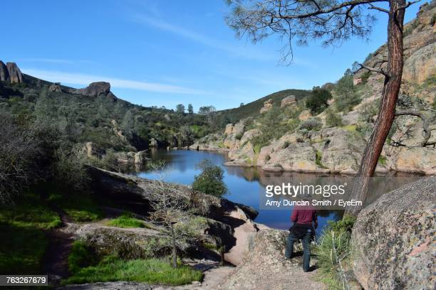Rear View Of Man Standing On Rock By Lake During Sunny Day