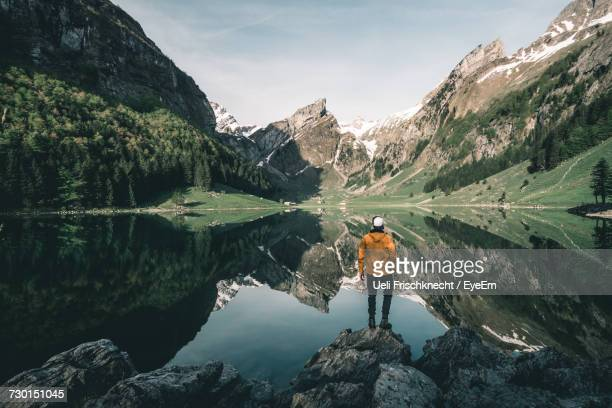 rear view of man standing on rock by lake - lago reflection foto e immagini stock