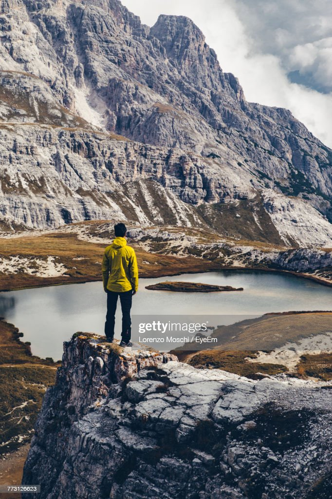 Rear View Of Man Standing On Rock By Lake : Photo