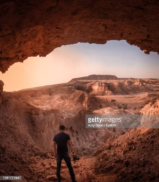 rear view of man standing on rock - riyadh stock pictures, royalty-free photos & images