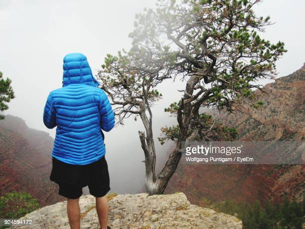Rear View Of Man Standing On Rock Sky During Foggy Weather