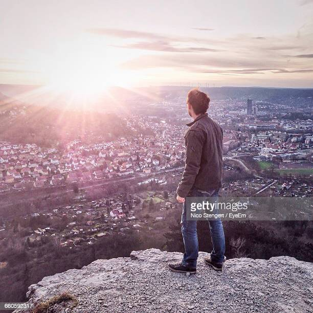 Rear View Of Man Standing On Rock While Looking At Town Against Sky