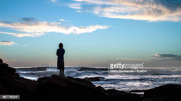 Rear View Of Man Standing On Rocks By Sea Against Sky