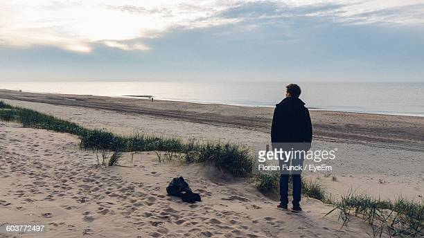 Rear View Of Man Standing On Sandy Beach Against Sky