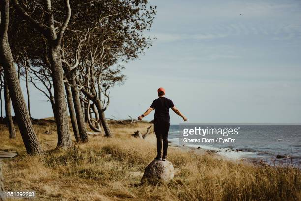 rear view of man standing on shore against sky - funen stock pictures, royalty-free photos & images