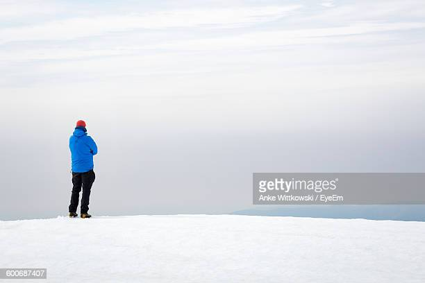 Rear View Of Man Standing On Snow Covered Field Against Sky