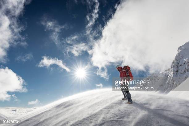 rear view of man standing on snow covered mountain - fabrizio zampetti foto e immagini stock
