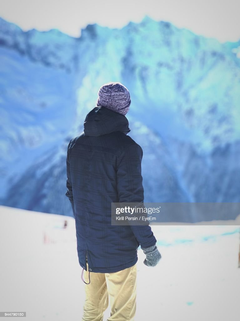 Rear View Of Man Standing On Snowcapped Mountain : Stock Photo