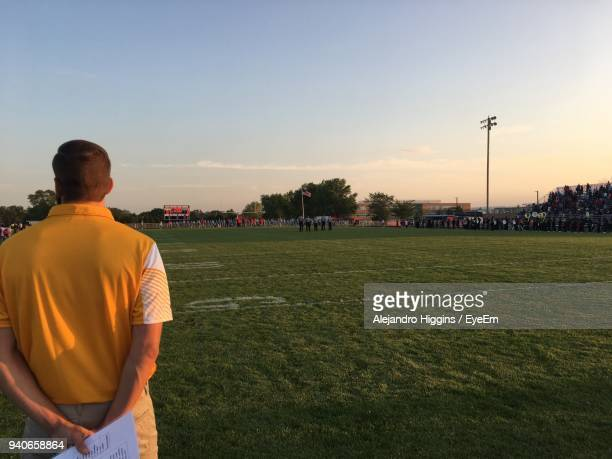 Rear View Of Man Standing On Sports Field Against Sky During Sunset