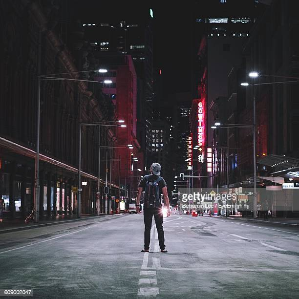 rear view of man standing on street amidst buildings at night - night stockfoto's en -beelden