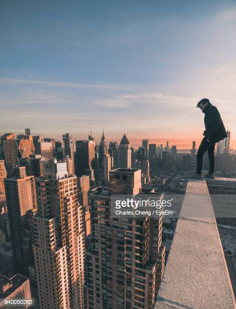 Rear View Of Man Standing On Terrace By Cityscape Against Sky During Sunset
