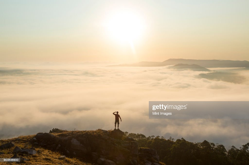 Rear view of man standing on top of mountain, admiring landscape view across misty valley. : Stock Photo