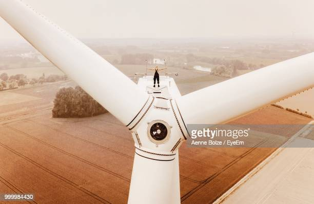 rear view of man standing on windmill - windmills stock photos and pictures