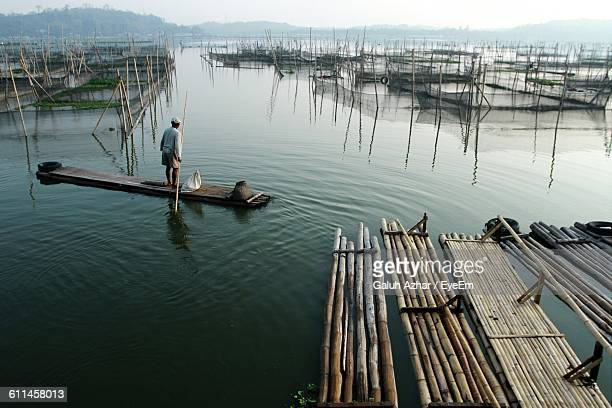 Rear View Of Man Standing On Wooden Raft In Sea