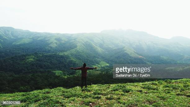 Rear View Of Man Standing With Arms Outstretched On Mountain Against Sky