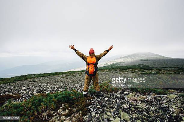 Rear view of man standing with arms outstretched on mountain