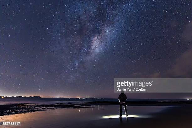 rear view of man standing with illuminated flashlight on shore against milky way - majestic stock pictures, royalty-free photos & images