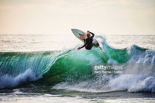 rear view of man surfing on waves against sky - wassersport stock-fotos und bilder