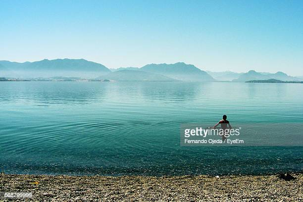 Rear View Of Man Swimming In Lake Against Clear Sky
