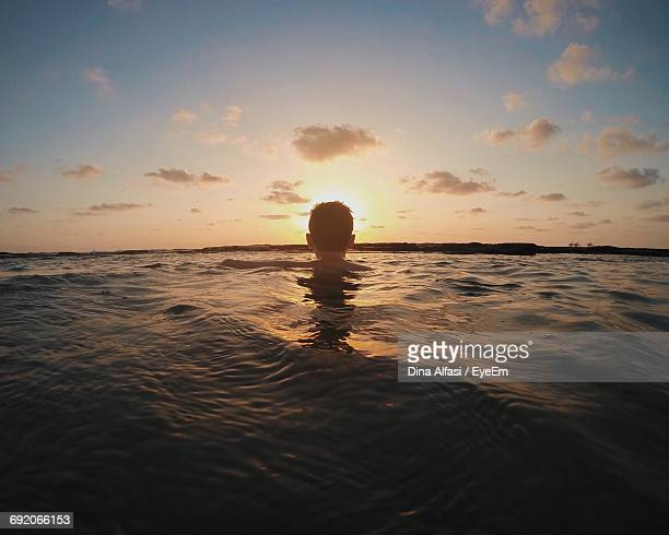 Rear View Of Man Swimming In Sea Against Sky During Sunset