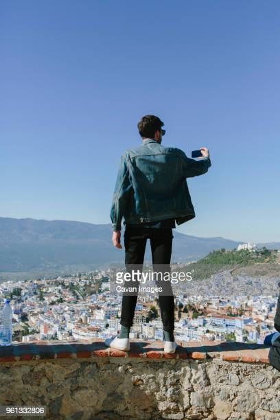 rear view of man taking selfie while standing on retaining wall against cityscape - capturing an image stock pictures, royalty-free photos & images