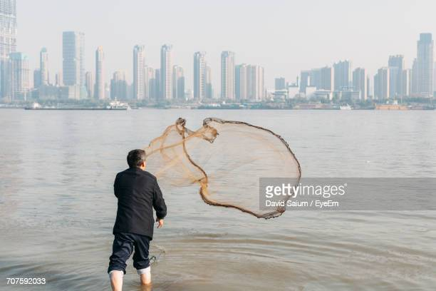rear view of man throwing fishing net in yangtze river by city - wuhan stock photos and pictures