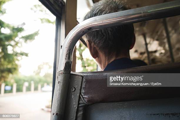 Rear View Of Man Traveling In Bus