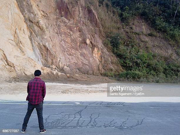 Rear View Of Man Urinating On Street