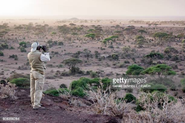 rear view of man using binoculars on cliff - arusha national park stock photos and pictures